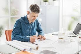 professional office desk. Professional Architect Working At Office Desk, He Is Drawing And Making Measurements On A Project Desk