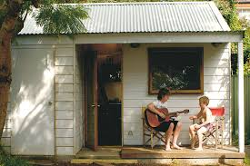 build a backyard cabin two boys in front of an outdoor cabin