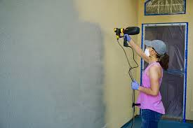 painting a house with a paint sprayer