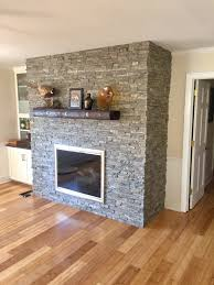 brick living room fireplace covered in panels that look like real stone