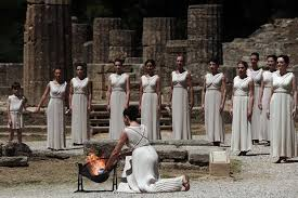 flame lighting olympics. the high priestess holds torch with olympic flame on may 9, 2012 during lighting ceremony in ancient olympia sanctuary where olympics y