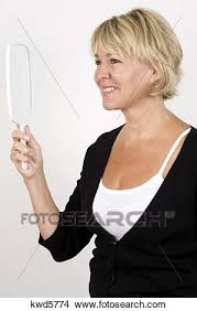 Stock Photo of Mature woman holding hand mirror smiling kwd5774