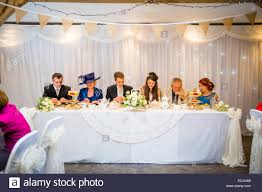 Getting married / Wedding day UK: The bride and groom at the top table  enjoying