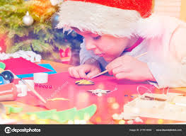 little boy in santa s hat sitting at the desk in the kindergarten and decorating wooden angel with yellow paint photo by serrnovik