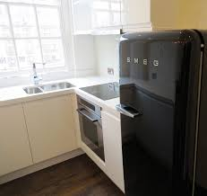 black refrigerator in kitchen. the clean contemporary vibe can also be seen in kitchen with this jet black smeg refrigerator. against white brick, glossy cabinets and dark wood refrigerator g