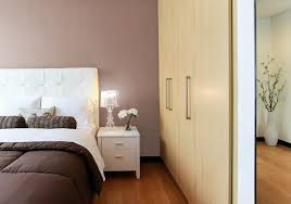 a minimalistic bedroom with a brown bedspread and white nightstand with a mauve colored wall