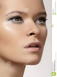 beautiful fashion model face with winter make up snow eyelashes shiny pure skin