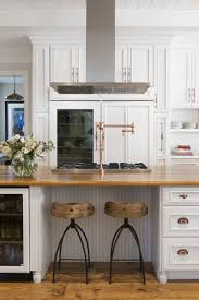 kitchen design entertaining includes: across from the range is seating near a beverage cooler for guests to mingle while the host prepares meals