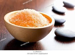 orange bath salt in wooden bowl