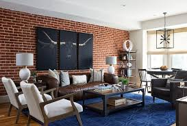 a plus brown leather sofa accented with white and gray pillows sits on a bold blue rug beneath a steer triptych art hung from a red brick wall