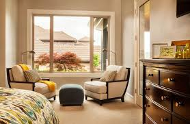 the master bedroom also has a sitting area near the large window on the right is a beautiful dark wood dresser and the door to the walk in closet