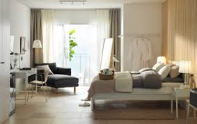 White and wood hotel room with bed, desk, chaise lounges and a sea view