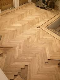 prime grade oak parquet floor with a walnut tramline being laid in the hallway