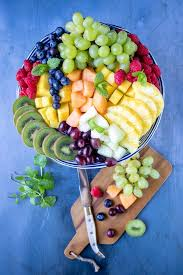 fruit platter served on a cake stand surrounded by chopped fruit salad ings on a blue