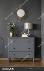 gold mirror grey wall cabinet lamp plant living room interior stock photo