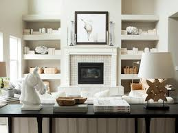 gorgeous monochromatic living room with floating shelves filled with whatnots filling alcoves on either side of fireplace and hearth
