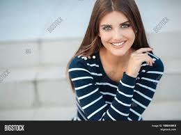 spring portrait of a happy brunette woman with long straight hair and gray green eyes