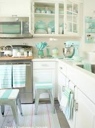 All white farmhouse kitchen with a narrow, space saving island and plank  wood counter tops.