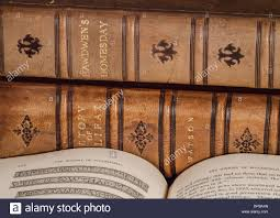 old history books in brown leather binding with one open showing history based text