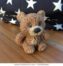 photo of a teddy bear toy sitting on a blue background with stars wallpaper lonely