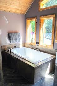 rustic purple bathroom with wood trimmed windows and large bathtub