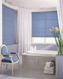 classic blue arm chair plus table decoration and beautiful flower filled on fancy bathroom designed with window treatment and oval bathtub