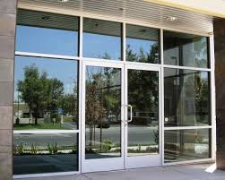 one way swing door with reflective bronze glass and transom header sides are fixed glasses
