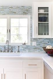 white cabinets small blue tiles all over and white quartz countertops
