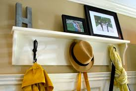 interior white wooden wall coat rack shelf with three hangers on the wall connected by