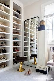 glam closet with black curved leaning mirror and gold and black stool