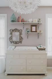 white changing table with storage shelves above it