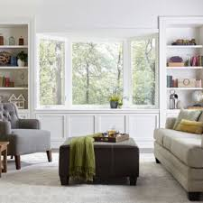 window chair furniture. Bay Window In A Room With White Walls, Bookshelves, Gray Cushioned Chair  And Furniture