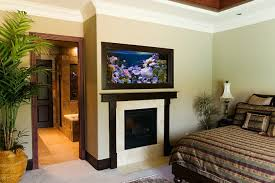 View in gallery Aquarium above fireplace in bedroom
