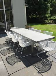 modern metal furniture. A Modern Concrete Table And White Metal Chairs For Simple Dining Space Furniture G