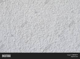 background of a white stucco coated and painted exterior rough cast of cement and concrete wall