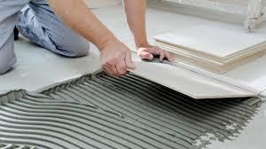 flooring installer laying a tile floor