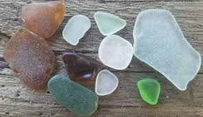 green sea glass brown sea glass clear sea glass on driftwood background from