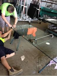 lying on the floor attaching panic bars for the new frameless glass doors at the gold coast turf club