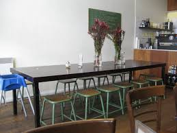 Long Narrow Black Dining Table With Glass Flower Vase Centerpieces And  Metal Stools ...