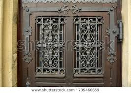 close up of a old door with windows covered by hand made iron grille grate