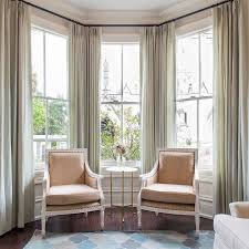 Sophisticated sitting room features a bay window dressed in gray green  drapes filled with beige bergere chairs and a round marble and brass table  atop wood ...