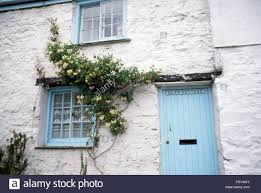 exterior of white painted cottage with a pale blue front door and windows