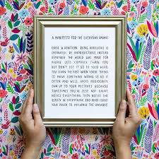 hands holding a frame with an inspirational print on a colorful background