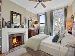 classic fireplace and superb ceiling fan for master bedroom with large white windows and light gray curtains