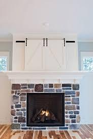 custom barn doors hide tv above fireplace by gowler homes gowlerhomes com
