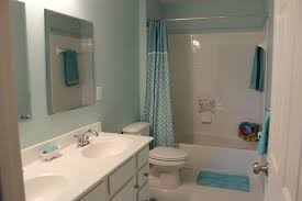 bathroom paint ideas blue with white wall tiles for white bathtub and soft curtains in front of white vanity table has gray cabinet under double frameless