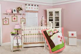 modern crib in light pink wall with soft cream flooring with owl bedding pattern
