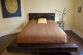 low profile dark brown wooden bed with head board also brown bedding set