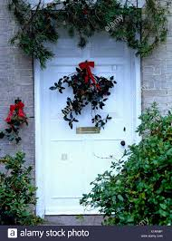 Christmas Conifer Garland Above White Front Door With Spray Of Holly Tied Red Ribbon