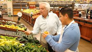 Produce Manager Produce Manager Assists Senior Adult Customer In Supermarket Art Print